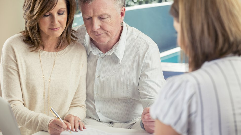Older couple signing papers
