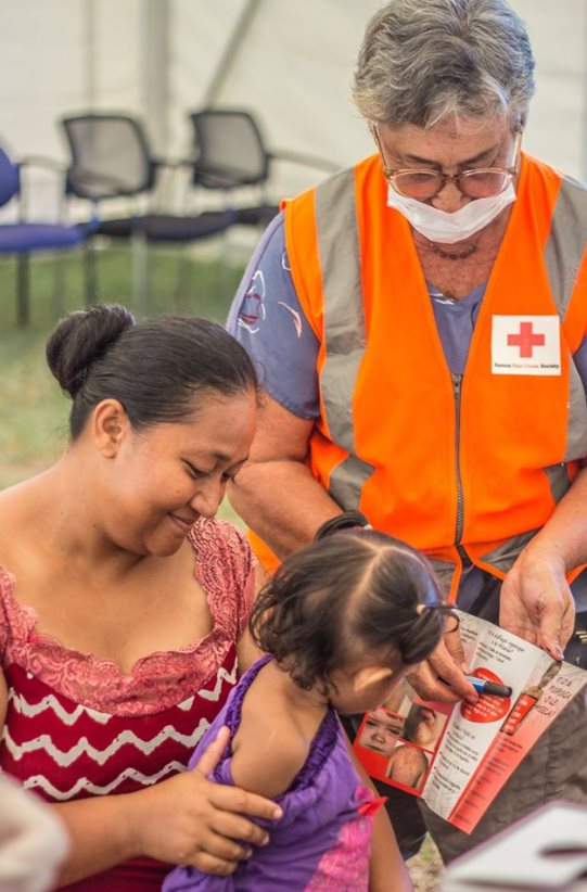 Una mujer y una niña reciben información sobre vacunación