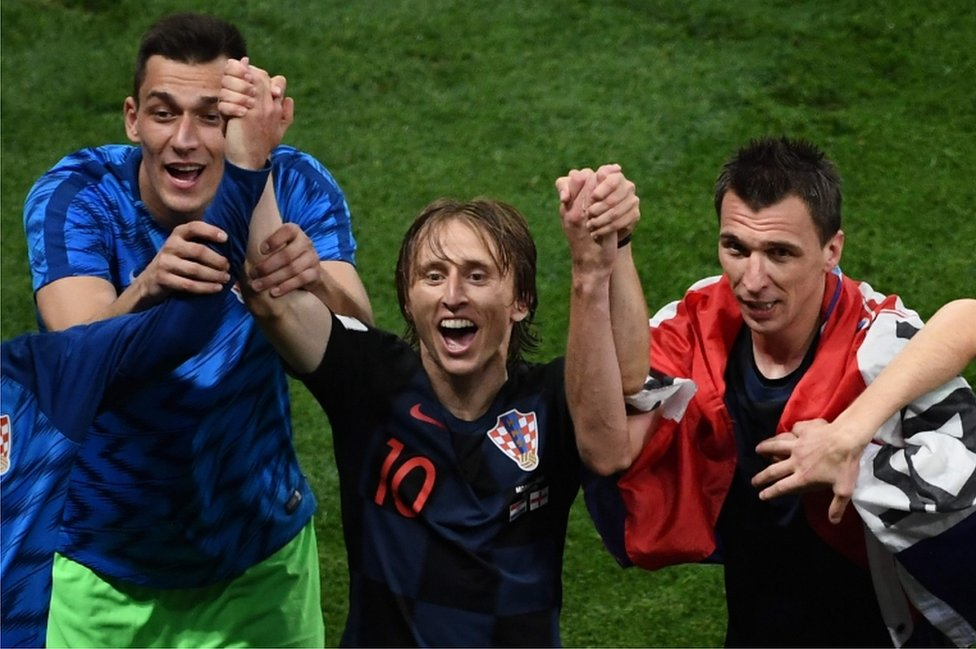 Croatia's midfielder Luka Modric (C) and Croatia's forward Mario Mandzukic (R) celebrate after winning the Russia 2018 World Cup semi-final football match between Croatia and England at the Luzhniki Stadium in Moscow on 11 July 2018.