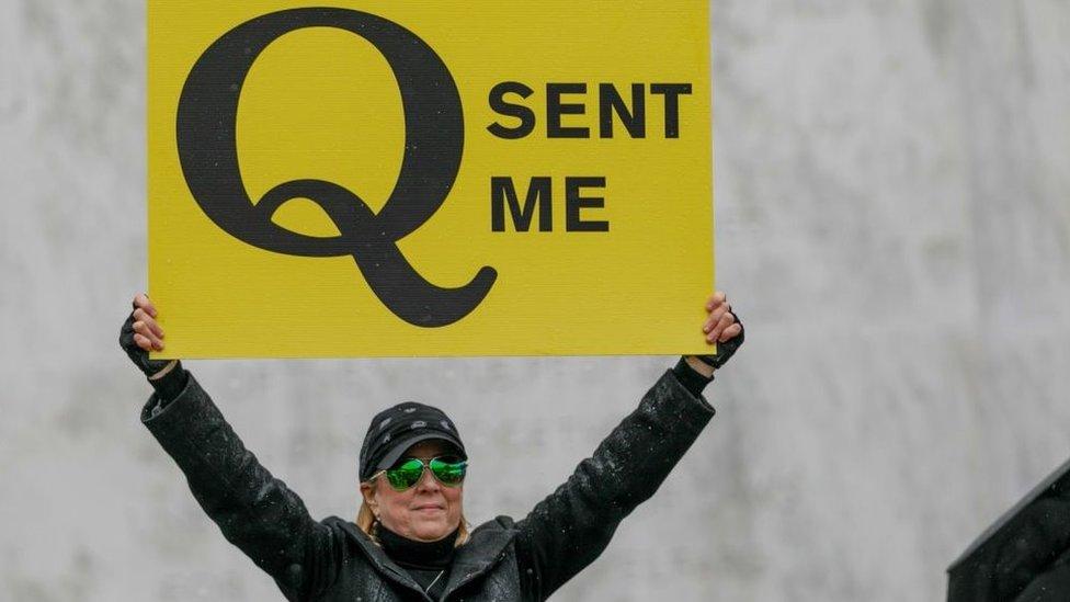Mulher com cartaz em que se lê: O Q me mandou aqui