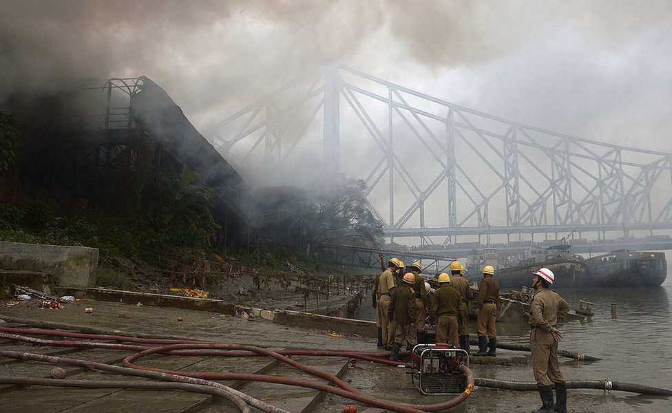 The Howrah bridge is pictured in the background as smoke rises from a burning godown in Kolkata on January 3, 2013.