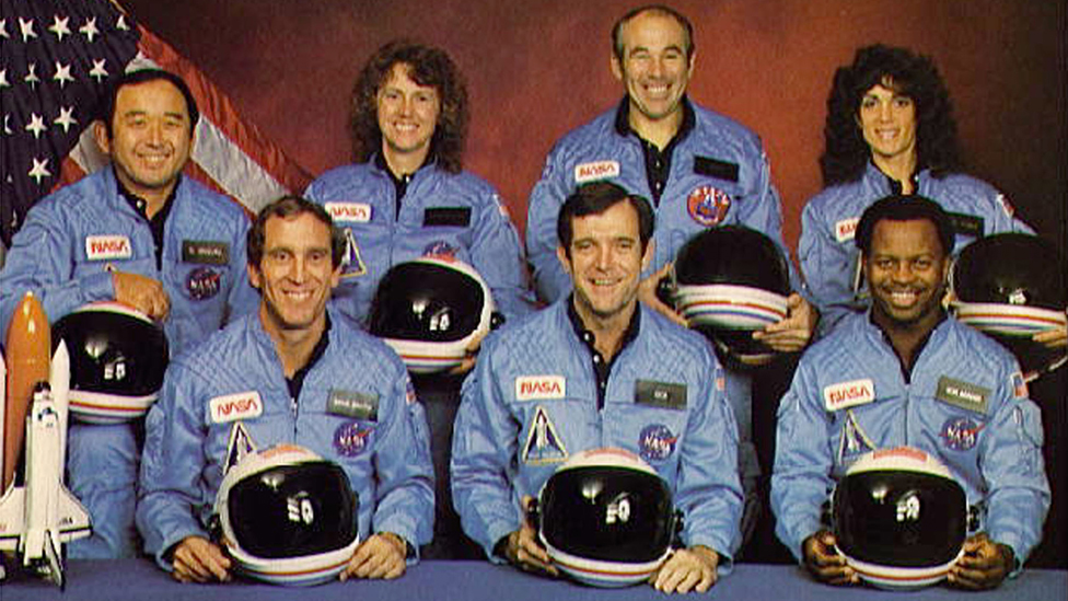 Space Shuttle Challenger crew members gather for an official portrait November 11, 1985 in an unspecified location. (Back, L-R) Mission Specialist Ellison S. Onizuka, Teacher-in-Space participant Sharon Christa McAuliffe, Payload Specialist Greg Jarvis and mission specialist Judy Resnick. (Front, L-R) Pilot Mike Smith, commander Dick Scobee and mission specialist Ron McNair.