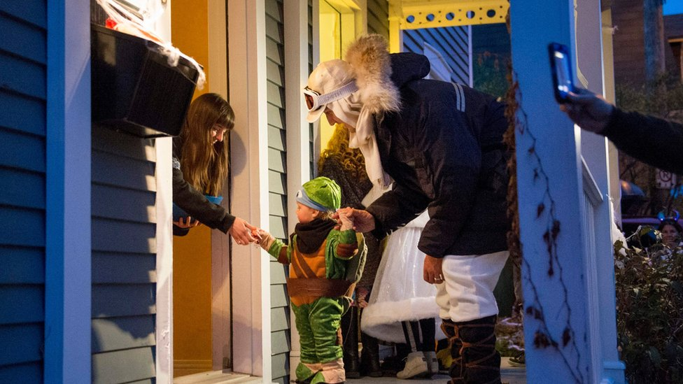Mr Trudeau and his child at a door receiving candy