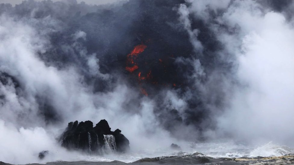 A steam plume rises as lava (C) enters the Pacific Ocean, after flowing to the water from a Kilauea volcano fissure, on Hawaii's Big Island on May 20, 2018 near Pahoa, Hawaii.
