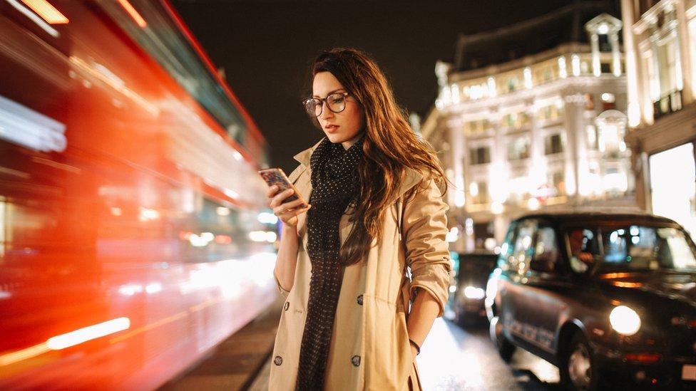 Mujer con el celular en la mano.