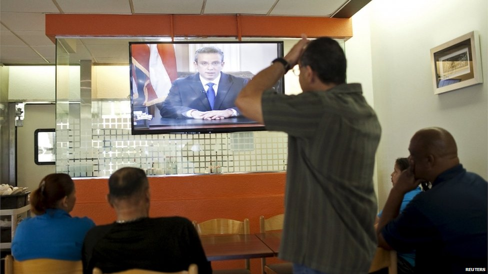 People sit in a restaurant while listening to an address by Governor Alejandro Garcia Padilla during a televised speech in San Juan, Puerto Rico, on 29 June 2015.