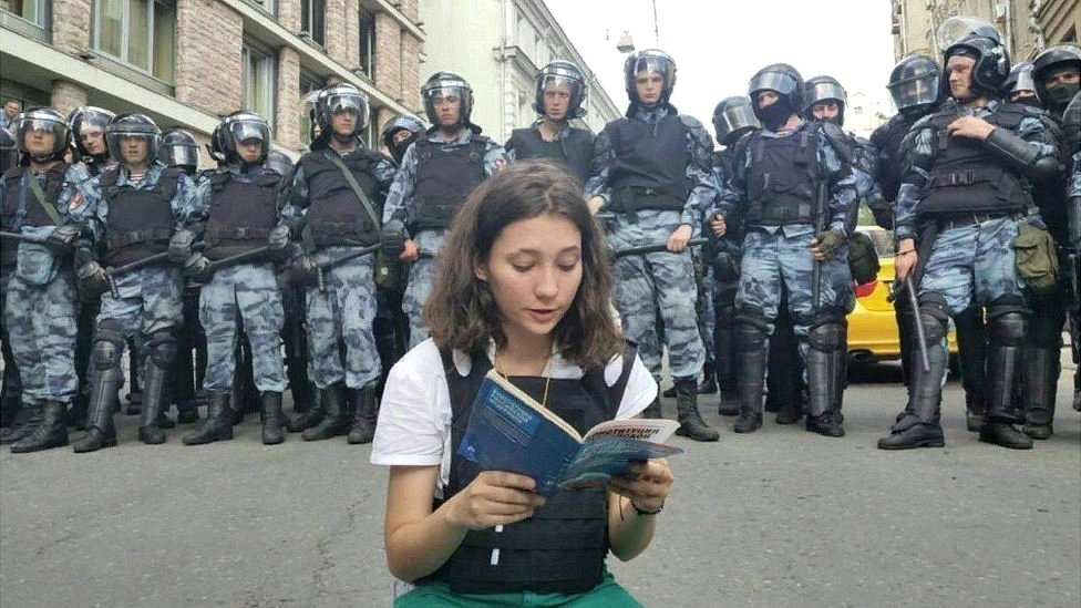 Olga Misik reads constitution as dozens of riot police stand behind her