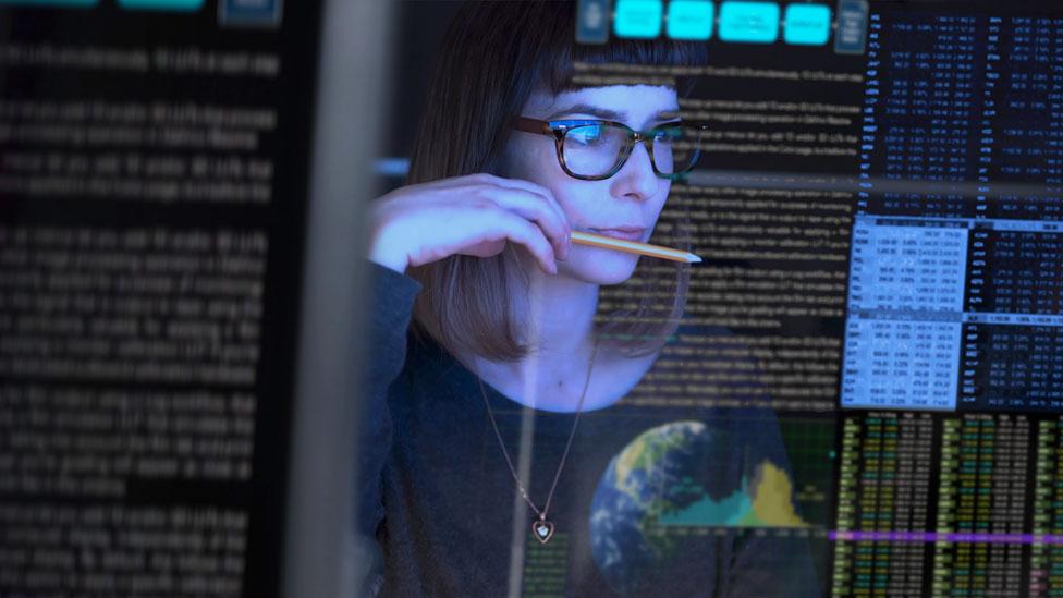 Una mujer mira a través de pantalla de computadora transparente