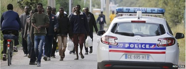 """French police patrol as migrants walk on a street near the makeshift camp called """"The Jungle"""" in Calais"""