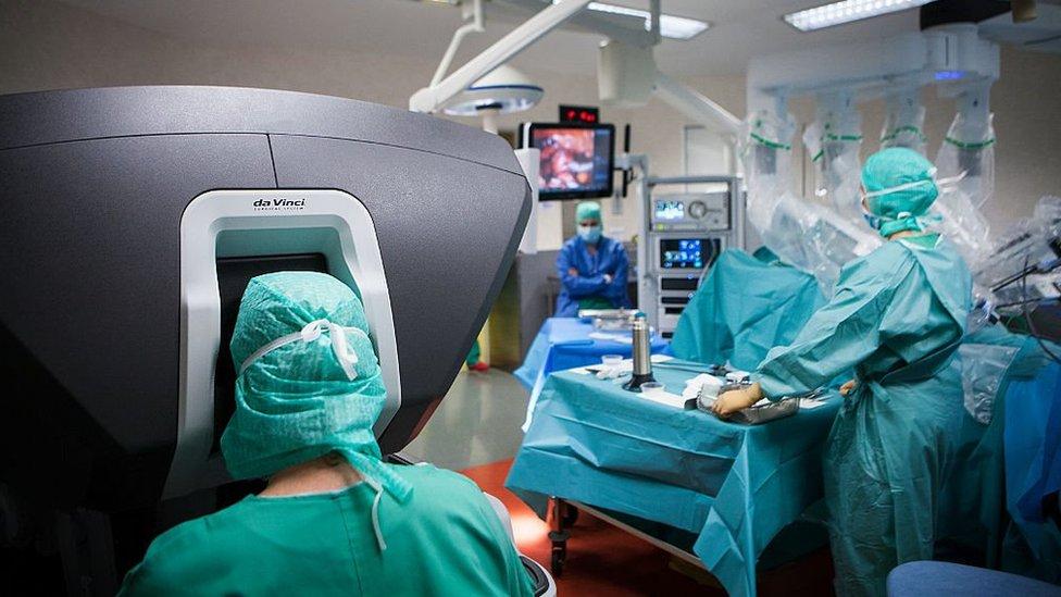 Un cirujano (izquierda) utiliza un robot quirúrgico da Vinci, controlado por una consola, para realizar una histerectomía