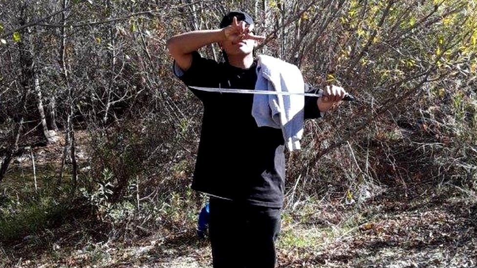 Un joven señalado como uno de los sospechosos de los delitos sostiene un machete y hace una señal con la mano característica de la MS-13
