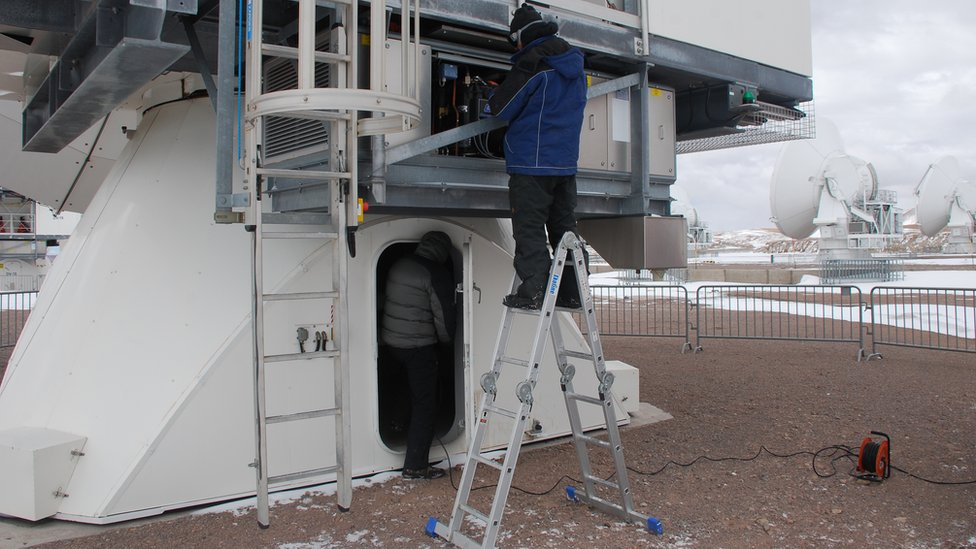 Engineers working on one of the dishes