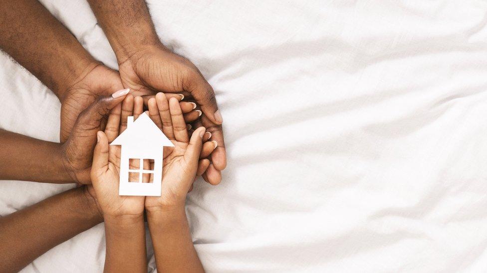 Manos de niños y adultos con una réplica de una casa.