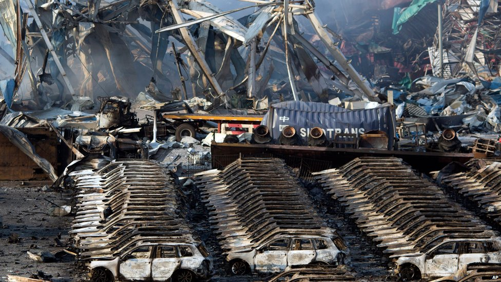 Charred remains of a warehouse and new cars are left burned after an explosion at a warehouse in Tianjin, Aug. 13, 2015