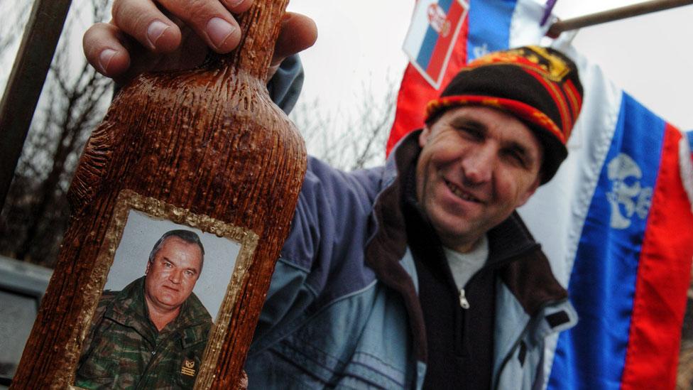 Hombre mostrando una botella de brandy que tiene la imagen de Ratko Mladic