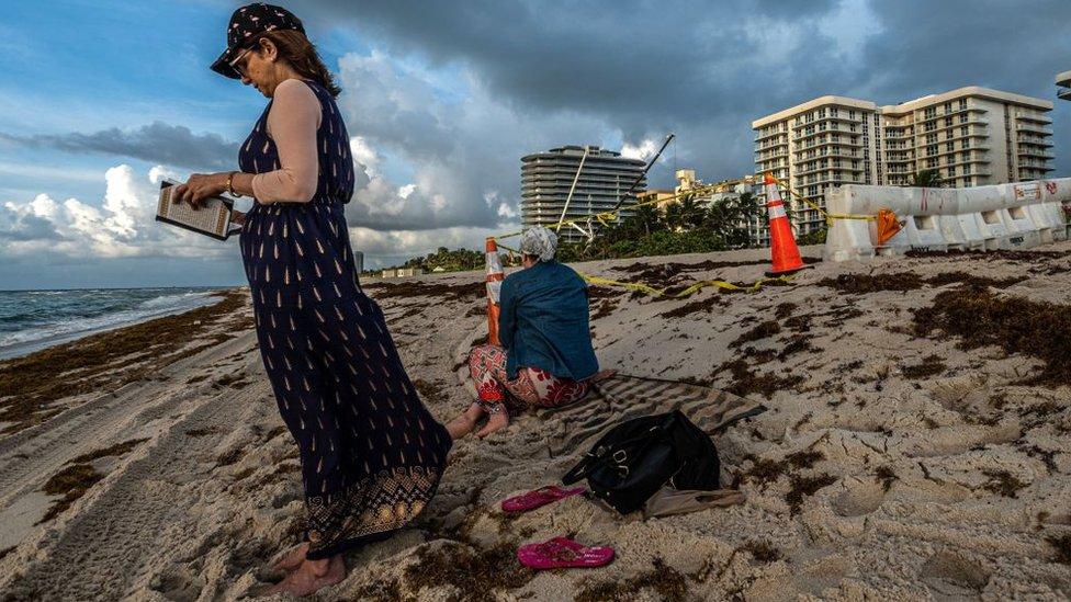 Una mujer rezando en hebreo tras la tragedia de Surfside.