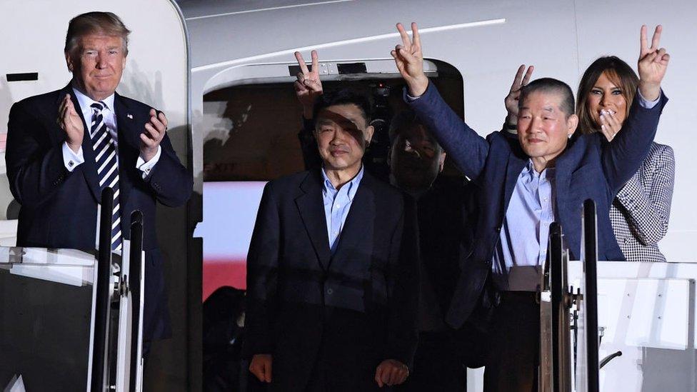 Trump y Melania Trump posan para las cámaras junto a los presos estadounidenses liberados en Corea del Norte.
