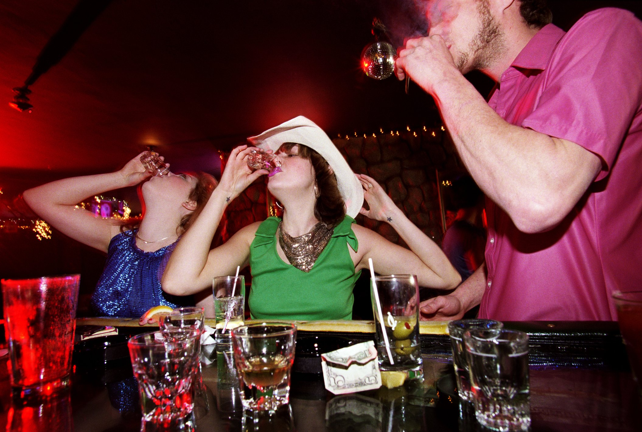 Dos mujeres y un hombre se alimentan a la fuerza en un bar