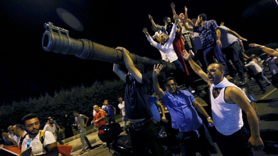 People stand on a tank during a failed coup attempt in Turkey