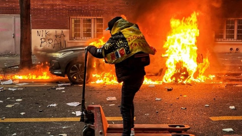 """A protester moves on a hand lift truck as a car is on fire during a protest against France""""s controversial global security law, in a street between Porte des Lilas and Gambetta square, in Paris, France, 05 December 2020"""