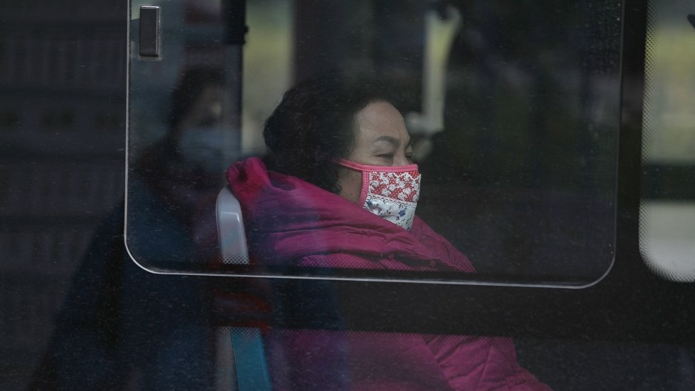 A woman wears a mask as she rides a bus near the closed Huanan Seafood Wholesale Market in China