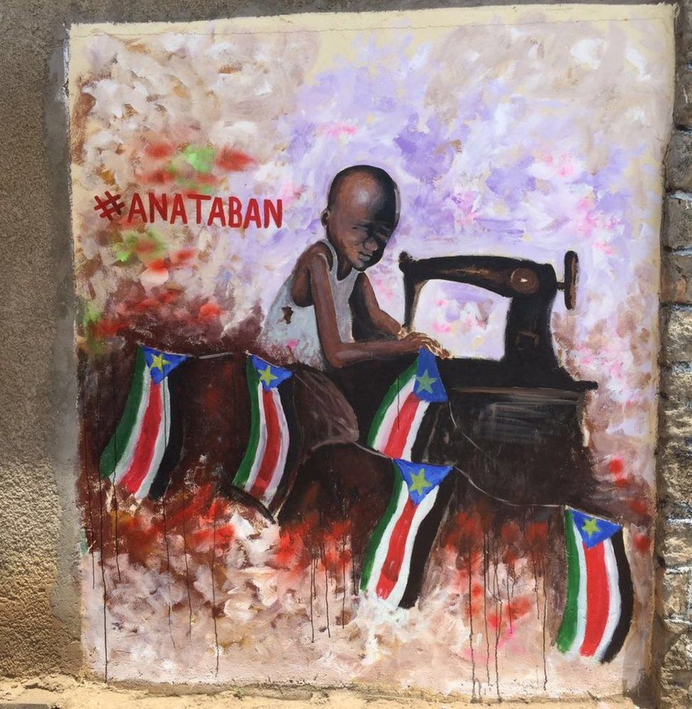Chil operates a sewing machine, which is stitching the South Sudan flag back together