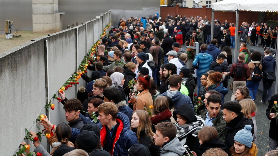 People place roses at the Wall memorial during a ceremony marking the 30th anniversary of the fall of the Berlin Wall at Bernauer Strasse in Berlin, Germany - November 9, 2019