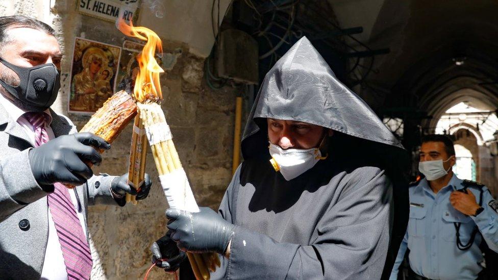 كاهن ينقل الشعلة في أحد شوارع القدس وهو يرتدي كمامة