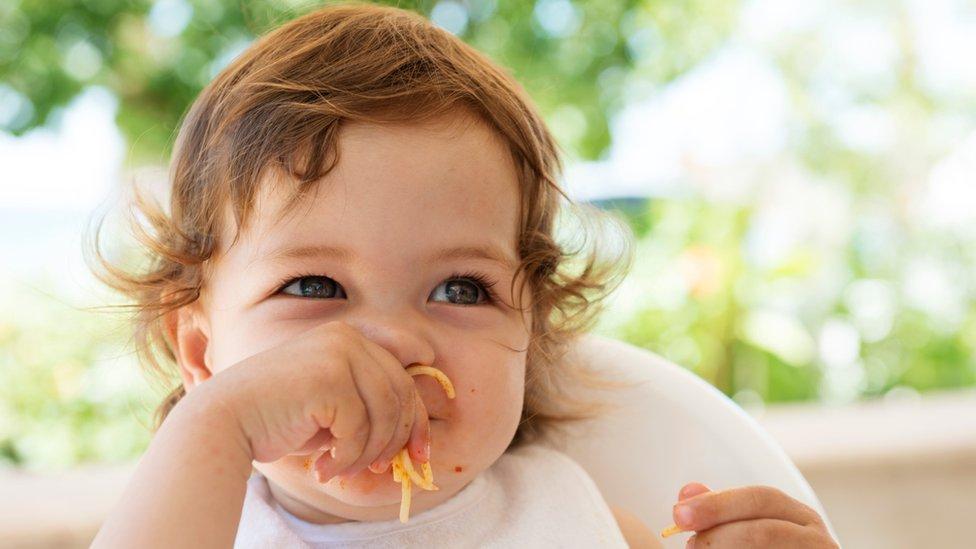 Niña comiendo fideos con la mano