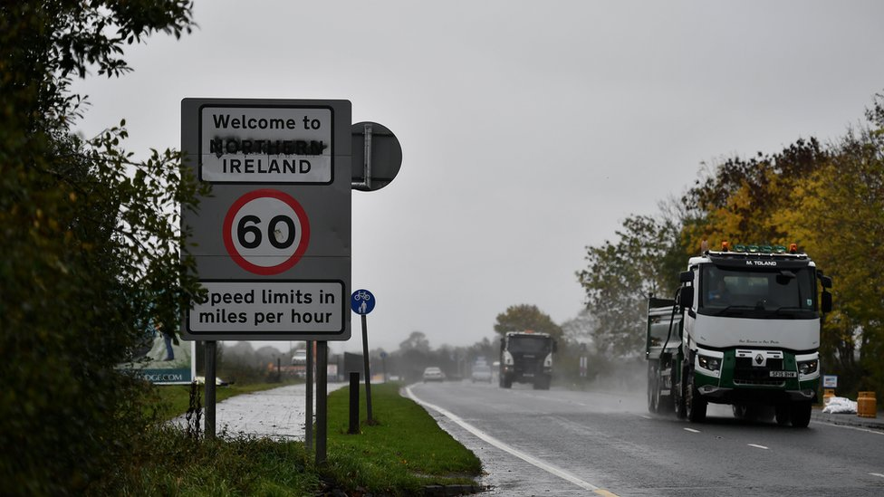 """Traffic moves by a defaced """"Welcome to Northern Ireland"""" sign on the Irish border on October 9, 2018"""