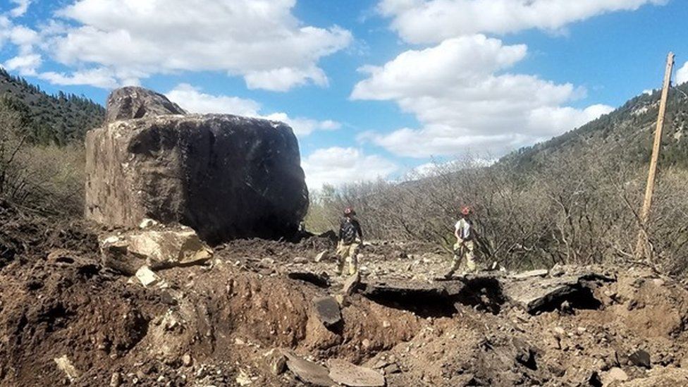 The section of the road that was destroyed by a rock slide containing two enormous boulders with two workers standing in the road.