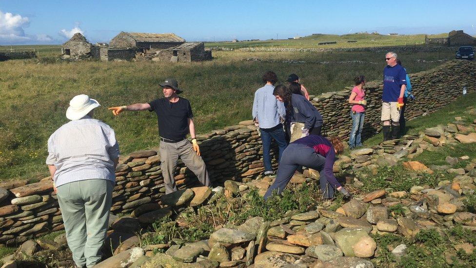 Volunteers work on stone dyke