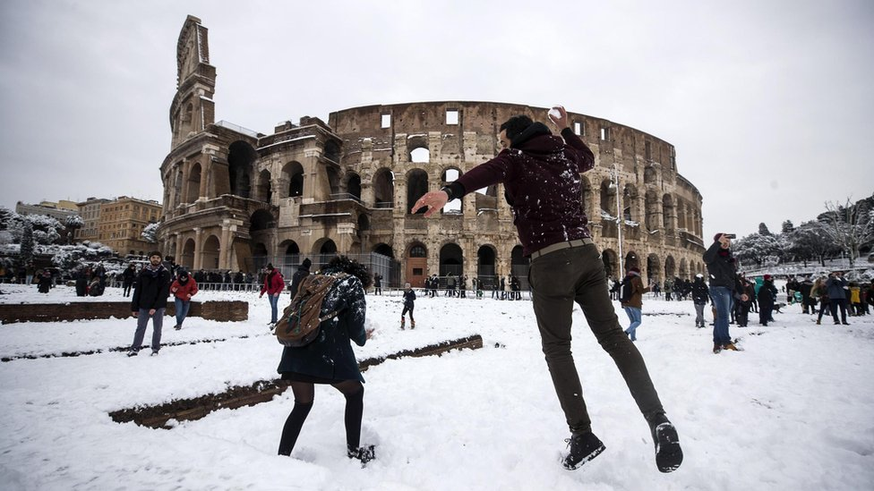 People take part in a snowball fight in front of the Colosseum covered by snow during a snowfall in Rome, Italy, 26 February 2018.