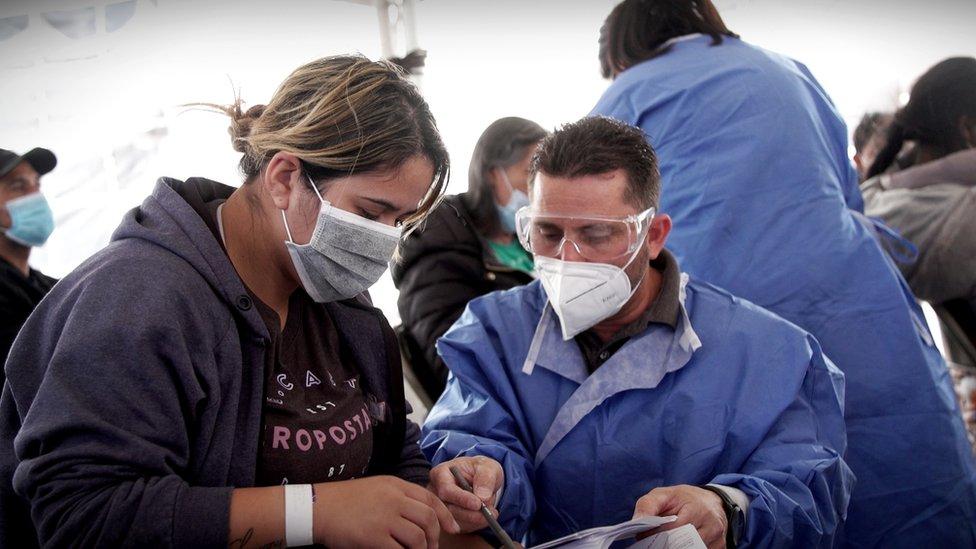 Fernando Quiroz ayudando a una migrante a llenar un formulario.