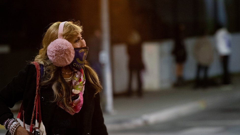 A woman wearing a protective face mask and earmuffs crosses the street during the outbreak of the coronavirus disease) in Beverly Hills, California, US, November 20, 2020