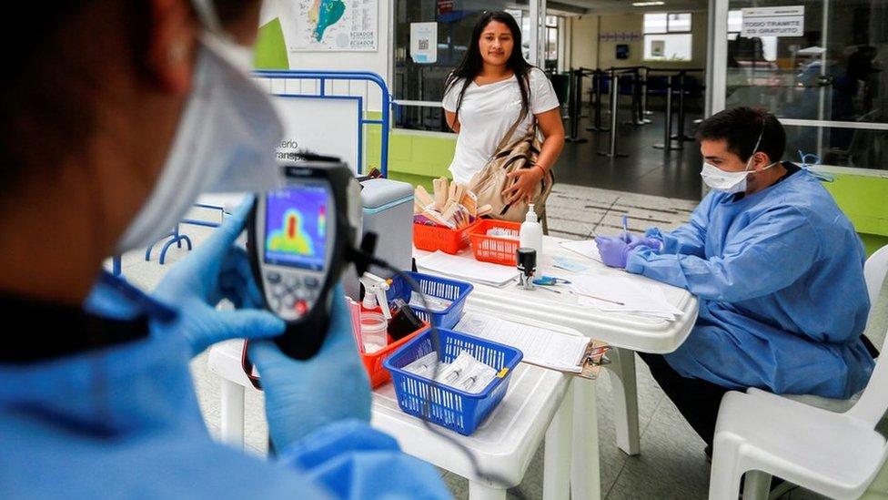Personal de salud tomando la temperatura de una viajera en la frontera de Ecuador con Perú.