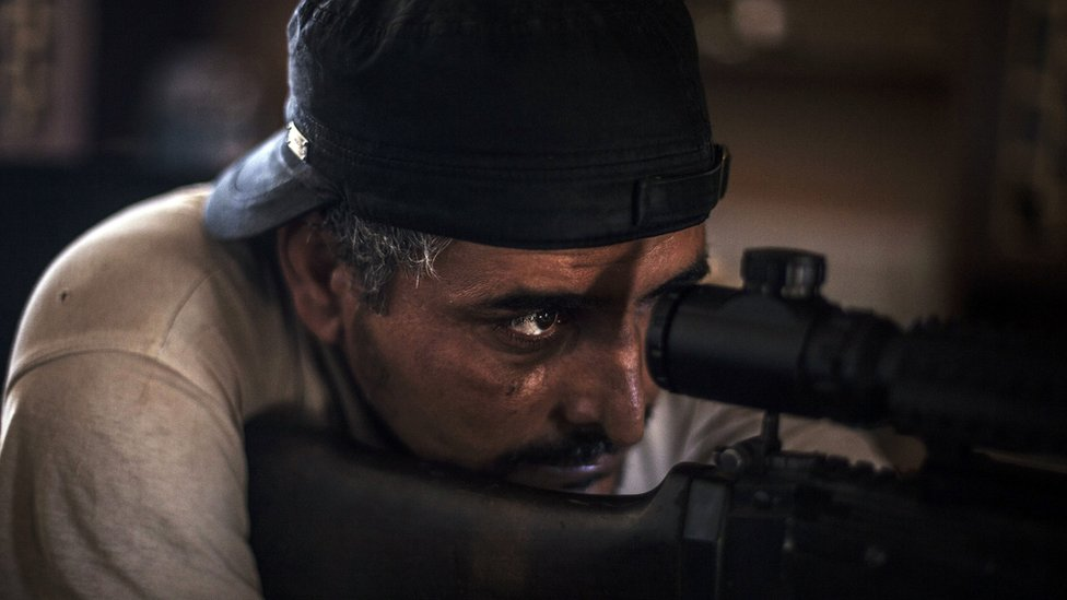 A fighter from forces affiliated to the Tripoli government scans for targets from his position in a building at the frontline in Sirte, Libya - Wednesday 28 September 2016