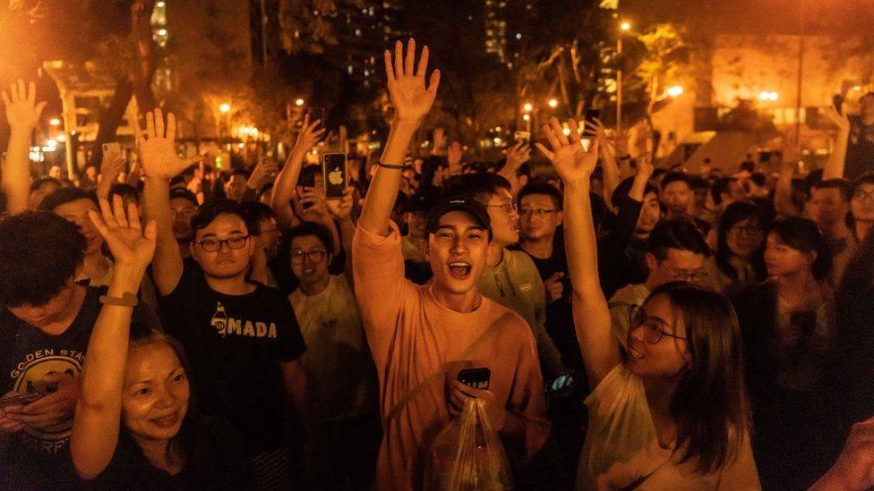 Jóvenes celebrando el triunfo de candidatos prodemocracia en Hong Kong.