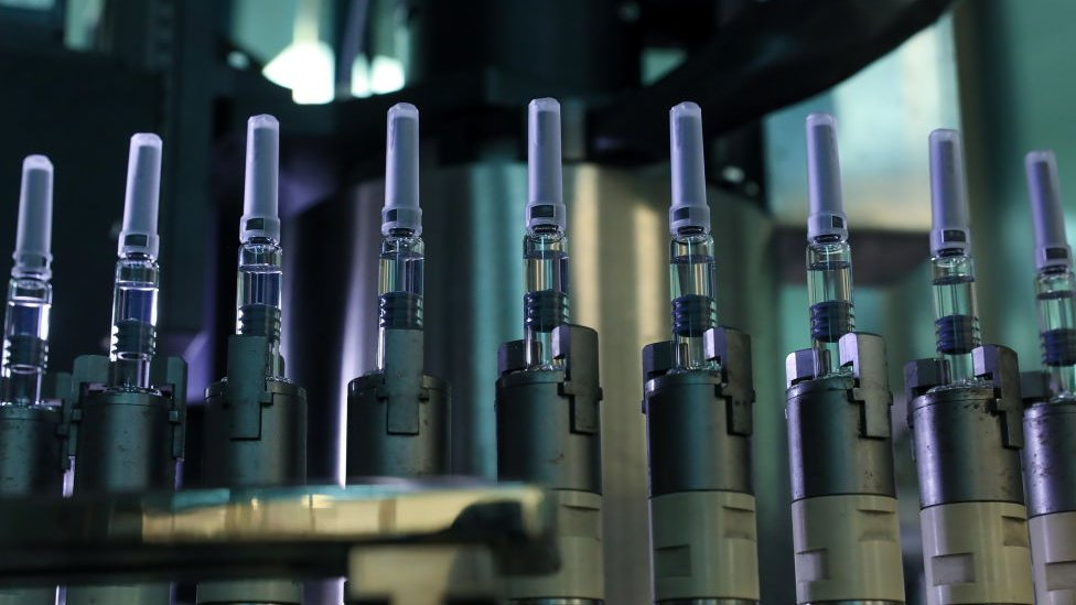 Vaccines vials on an assembly line