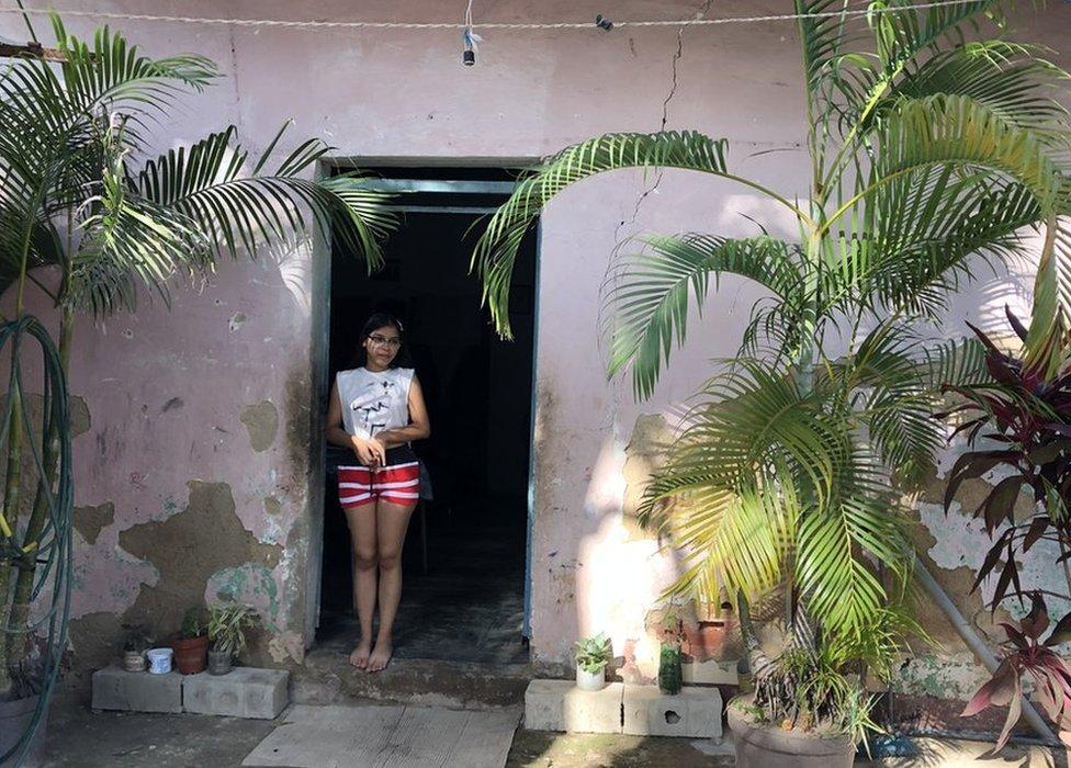 Valeria standing at the door of her home in La Pedrera, Maracay, Venezuela
