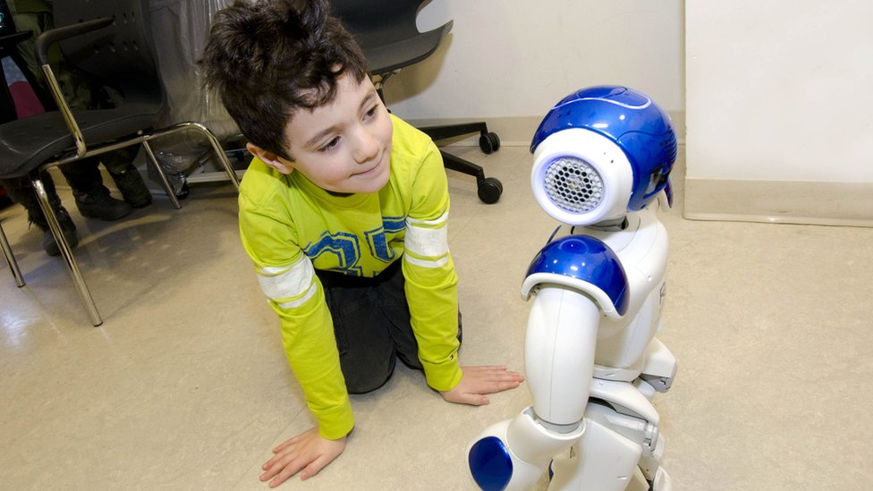 Boy kneeling and interacting with robot