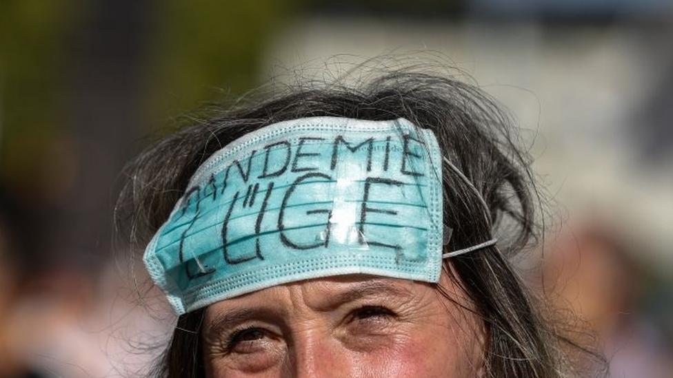 Manifestante en Berlín con una mascarilla en la frente en la que se lee: