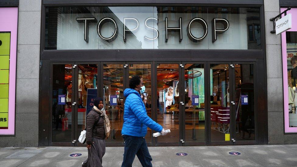 People walking past Topshop wearing face masks