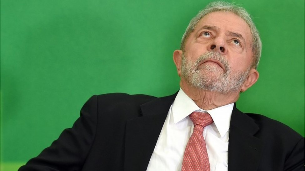 Former Brazilian president Luiz Inacio Lula da Silva gestures next to Brazilian president Dilma Rousseff (out of frame) after Lula's sworn in as chief of staff, in Brasilia on March 17, 2016