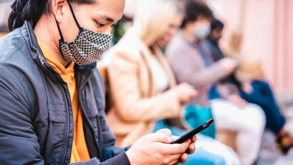 Personas con mascarilla mirando el teléfono.
