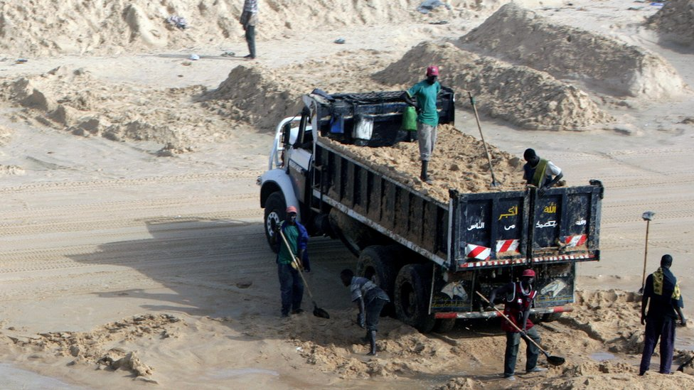 Men load a truck with sea sand on a beach in Senegal