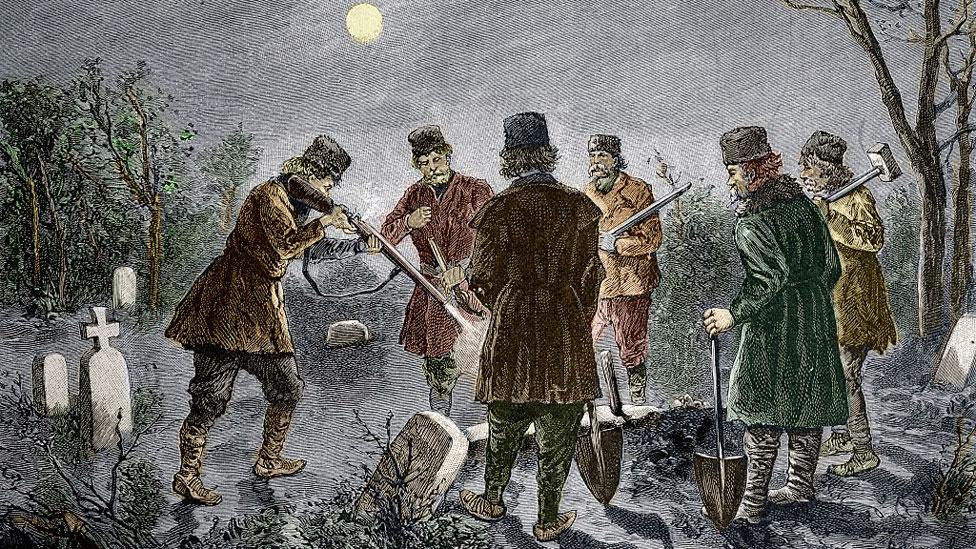 Grupo de hombres matando a un muerto en el cementerio