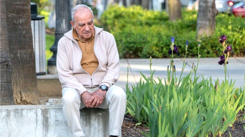 Elderly man sitting alone in a park