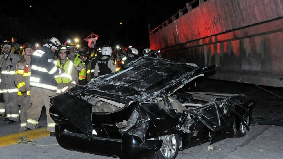 Rescue workers examine a destroyed car after the collapse of a bridge in Guayaquil, Ecuador