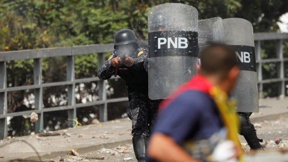 Policías apuntan a un manifestante